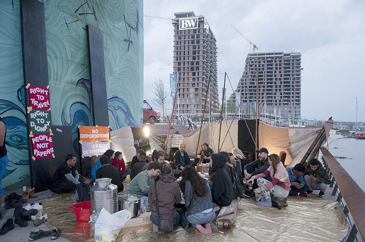 """Joar Nango, """"Longhouse Session"""", instalacija u Beogradu, deo umetnikovog rada """"European Everything"""" na Dokumenti 14, 2017. Umetnik je deo svog rada za ovogodišnju Dokumentu odlučio da realizuje na putu od Atine do Kasela i to na savskom keju, u blizini mesta na kome je nekad stajala baraka koju su naseljavale izbeglice, a koja je srušena radi izgradnje projekta """"Beograd na vodi"""". Na ovom mestu umetnik je skupa sa lokalnim umetnicima i aktivistima izgradio privremenu skulpturu-ambijent, kojim je pokušao simulirati baraku, ali ovog puta kao mesto kritičke refleksije zbog nepostojanja mesta susreta lokalnog stanovništva sa izbeglicama. Foto: Vladan Jeremić, 2017."""