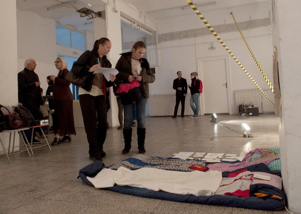 """Instalacija od crteža i rekvizita sa performansa Sofije Modošanov i Jelene Jaćimović, umetnica koje su sedam dana boravile u MSUB, izložena je u MKM-u na izložbi """"Razmere potkupljivosti"""", 27. oktobra, 2017. Performans koji su umetnice izvele se zvao """"7×24 = povratak kući"""", a one su želele """"maksimalno iskoristiti"""" i """"nadoknaditi"""" sve propušteno tokom 10 godina koliko je MSUB bio zatvoren, tako što su se preselile u njega za vreme sedmodnevnog svečanog otvaranja. Sofija Modošanov i Jelena Jaćimović su kasnije u radio emisiji izjavile da su """"prazni listovi papira izgleda bili najveća pretnja za muzej"""" i da im je obezbeđenje reklo da se """"političke konotacije"""" ne mogu unositi u muzejski prostor. Foto: DeMaterijalizacija umetnosti, 2017."""