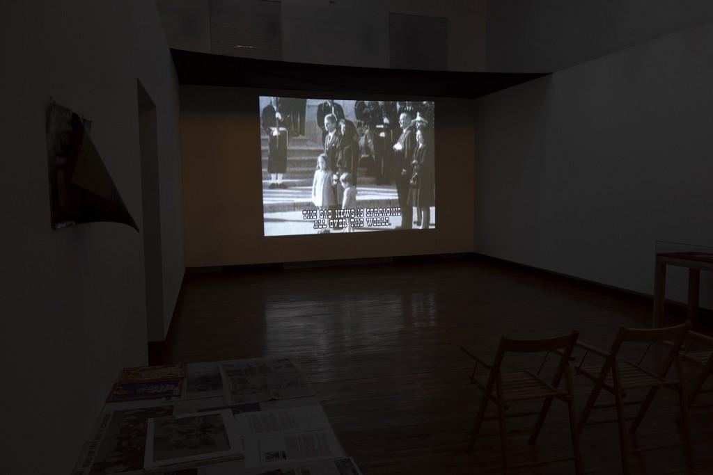"""Rad Zorana Naskovskog, """"Smrt u Dalasu"""", video instalacija izložena 2016. u Ateljeu Dado, Cetinje, crno-belo, boja, zvuk,16'42"""", rad je nastao 2001. godine. Na izložbi """"Smrt u Dalasu / dokumenti (2000-2016)"""" u Ateljeu Dado na Cetinju, pored video instalacije predstavljeni su i dokumenti koji se odnose kako na širi kontekst samog rada, tako i na njegovu recepciju u lokalnoj sredini, a koji ukazuju na niz manipulacija, kako u medijima tako i u okviru umetničkih institucija. Fotografija: Lazar Pejović, komentar: Zoran Naskovski."""